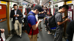 Young man stand in metro carriage, look to smart phone listen headphones Footage