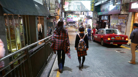 Two Asian girlfriends walk down night street, chase... Stock Video Footage