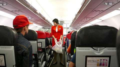 Stewardess in red suit collects rubbish plastic bag, walk... Stock Video Footage