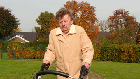 pensioner wheel walker in colorful autumn park walk through camera 4k 11762 Footage