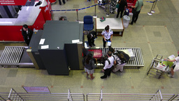 Passenger luggage scanned at X-ray, people entering airside terminal area Footage