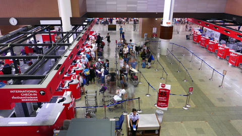 Travellers queue against check-in counter desks at terminal, timelapse Footage