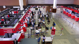 Passengers queue to check-in counters, airport concourse, time-lapse shot Footage