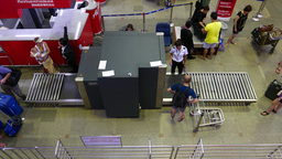 Passenger with luggage trolley wait his package pass through X-ray screening Footage