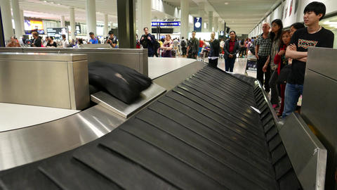Black soft bag slide down to luggage transporter from luggage outlet conveyor Footage