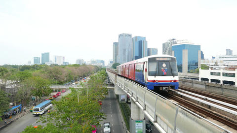 Colorful Skytrain move away along overground railway, central perspective view Footage