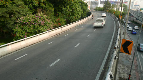 Cars sweep past over curved one way road going upwards, time lapse shot Footage