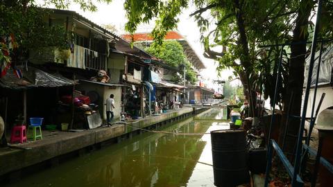 Slum aside tiny canal, old Bangkok, elderly man walk along concrete walkway Live Action