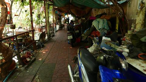 Slumming through narrow passage, man carry used plastic bottles bag Footage