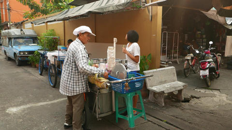 Aged thai women sell icecream from cart, tiny alley in city, parallax shot Footage
