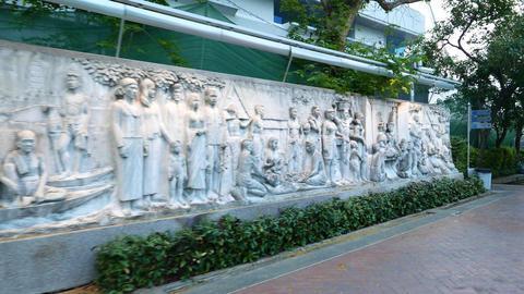 Bas-relief at Santi Chai Prakan Park illuminated in dusk, slide shot Footage