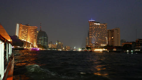 Night river side city view, tall skyscrapers with illuminated windows, travel Footage