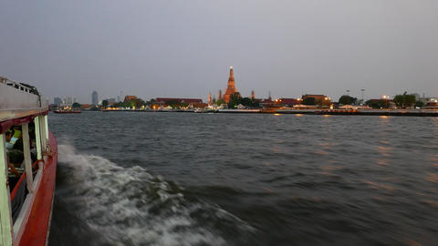 Chao Phraya river west bank at night, Wat Arun illuminated rise above, from boat Footage