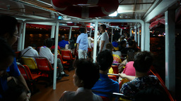 Express boat interior night time, passengers walk to exit at aisle, some sitting Footage