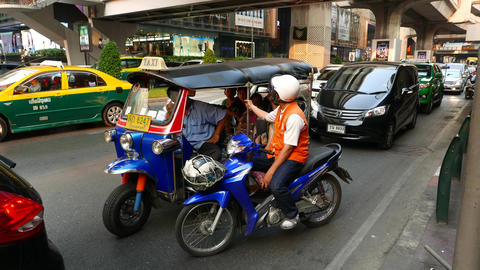 Motorcycle taxi driver talk with tuk-tuk passengers and cabby, stand on driveway Footage