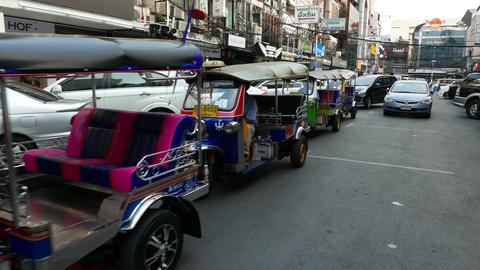 Car and tuk-tuk vehicles stand in queue waiting to exit local parking lot Footage