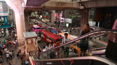 People travel up outdoor escalator, against crowded traffic on road, asian city Live Action