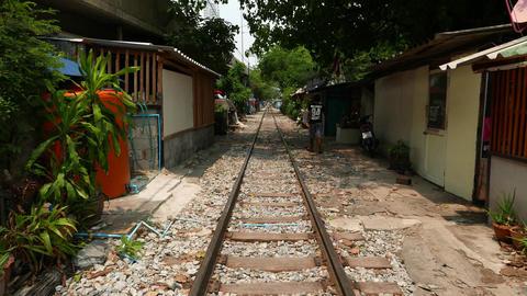 Follow Asian men walking along railway, slum shacks aside the way, glide shot Footage