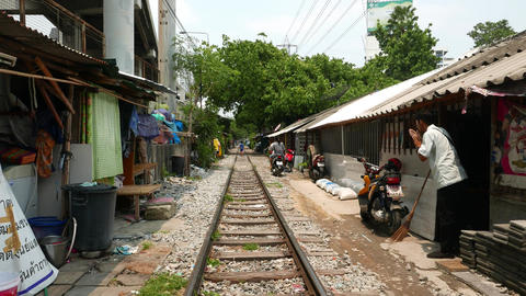 Man Sit Down After Motorcycle Driver And Ride Away, Slum Area Around Railroad stock footage
