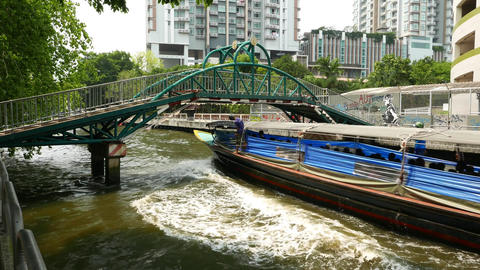 Express boat pass under footbridge and move away, as seen from shore Footage
