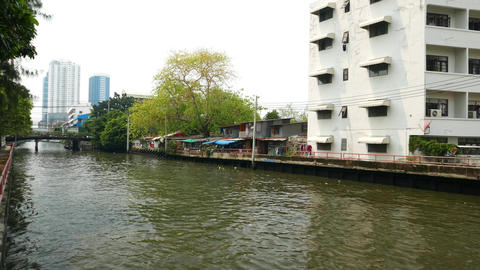 Canal bank, small hovels beside multi-storey dwelling house, truck shot Footage