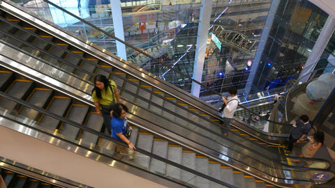 Escalators move up and down, modern glass wall, asian people travelling Live Action