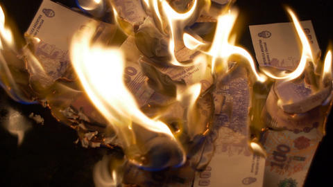 Burning 100 argentinian pesos bills Footage