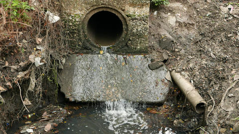 Sewage drain pipe outlet, water stream fall down to muddy puddle, white splashes Footage
