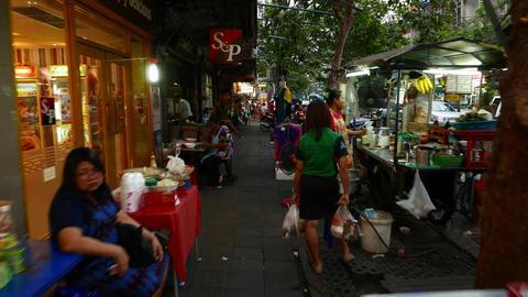Long POV walk along and through lively asian street sidewalk in dusk Footage