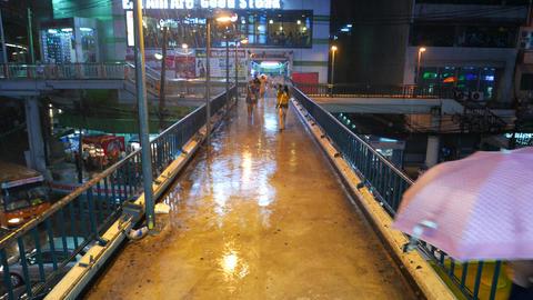 Woman run towards from rainfall over pedestrian bridge, urban night view Footage