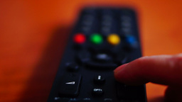 Remote Control. Hesitating Index Finger Touching The Channel Button On A Tv Remo stock footage