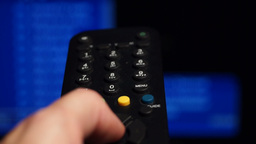 Remote control. Watching tv,changing channels, blurred TV, sound Footage