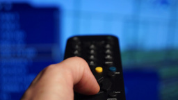 Remote control. Watching tv,changing channels, blurred TV Footage