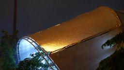 Rain water on illuminated tent roof, night tropical rainfall heavy showering Footage
