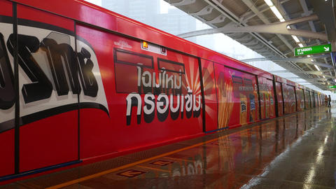Modern overground metro train arrive to empty platform, doors opens, heavy rain Footage