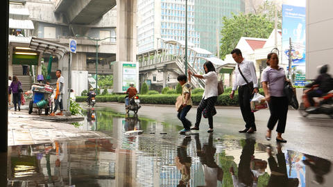 Family Crossing Puddle On Sidewalk, Woman Help Boy, Holding His Hand stock footage