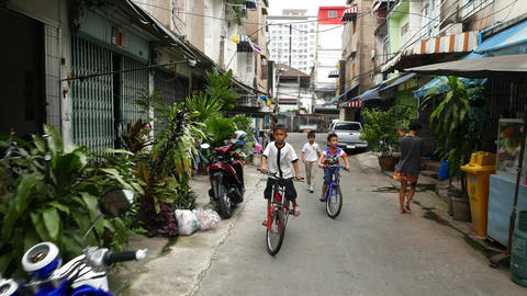 Small Thai boys on bicycles, small urbal street, old low-rise houses district Footage