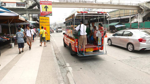 Man standing at song thaeo rear footplate, small baht bus standing on road Live Action
