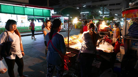 Mobile kitchen, street food on sticks, night alley near market, people waiting Footage