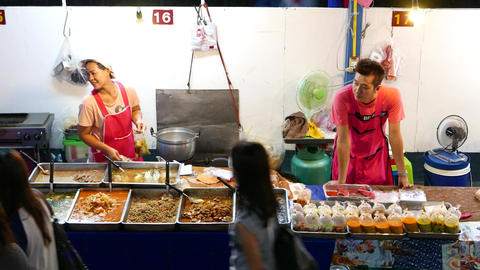 Stall full of trays with wet Thai dishes, night market, take home street food Footage
