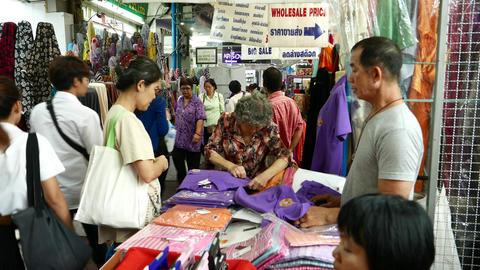 Aged woman examine violet polo t-shirt at Sampheng market, close view Footage