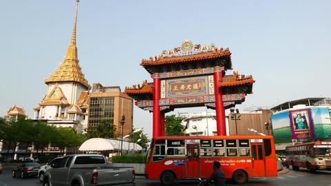 Odeon Circle Chinatown district gate and Wat Traimit on background, city traffic Footage