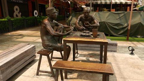 Docker lunch bronze sculpture at Asiatique, two men at table, parallax shot Footage