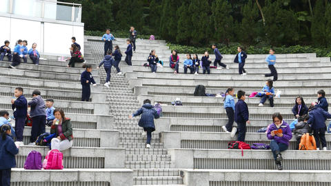 Small Chinese children run and gambol at amphitheatre steps, long slide shot ライブ動画