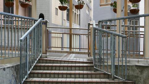 People pass pedestrian way, short staircase and walkway between escalators Footage