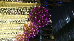 Purple decoration ball from plastic flowers, hanging in the night Footage