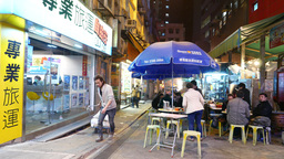 Loader drags cart on night street. Food area straight on the road Footage