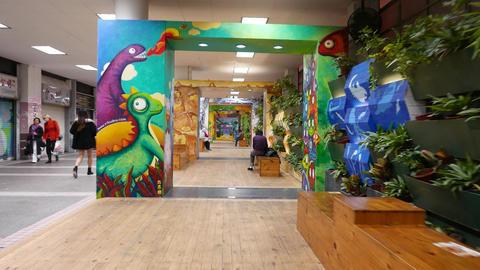Indoor rest area beside pedestrian passage, painted walls, artificial light Footage