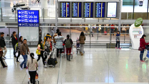 Group of chinese passengers stops near the timetable in airport Footage