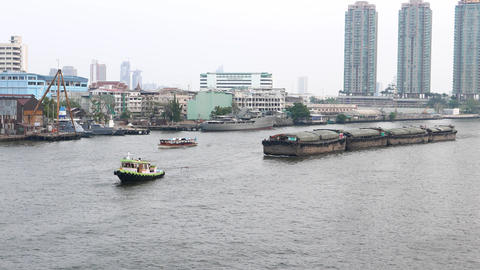 Tugboat tow four barge train, cityscape on back, Chao Phraya river near Taksin Footage
